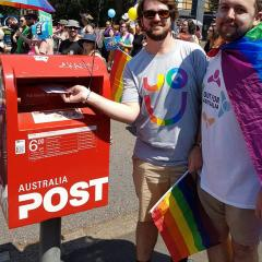 two men with rainbow pride flags posing in front of red post box